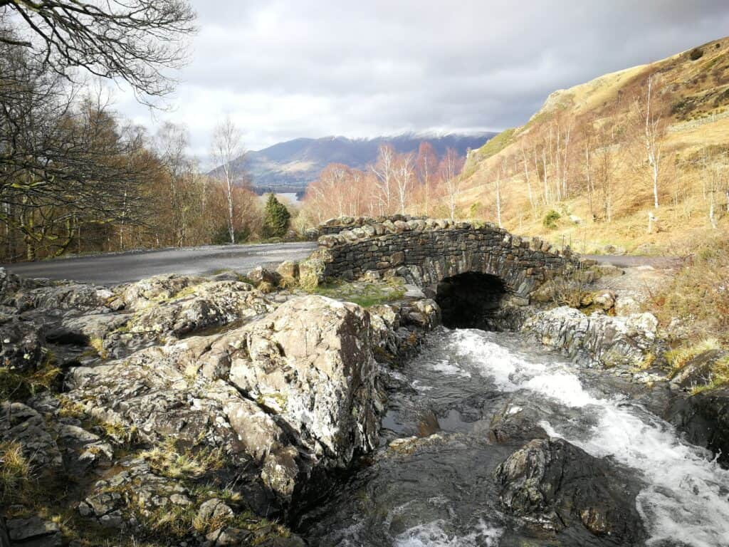 Ashness Bridge in the Lake District, with Barrow Beck running underneath. Views of the Wainwrights