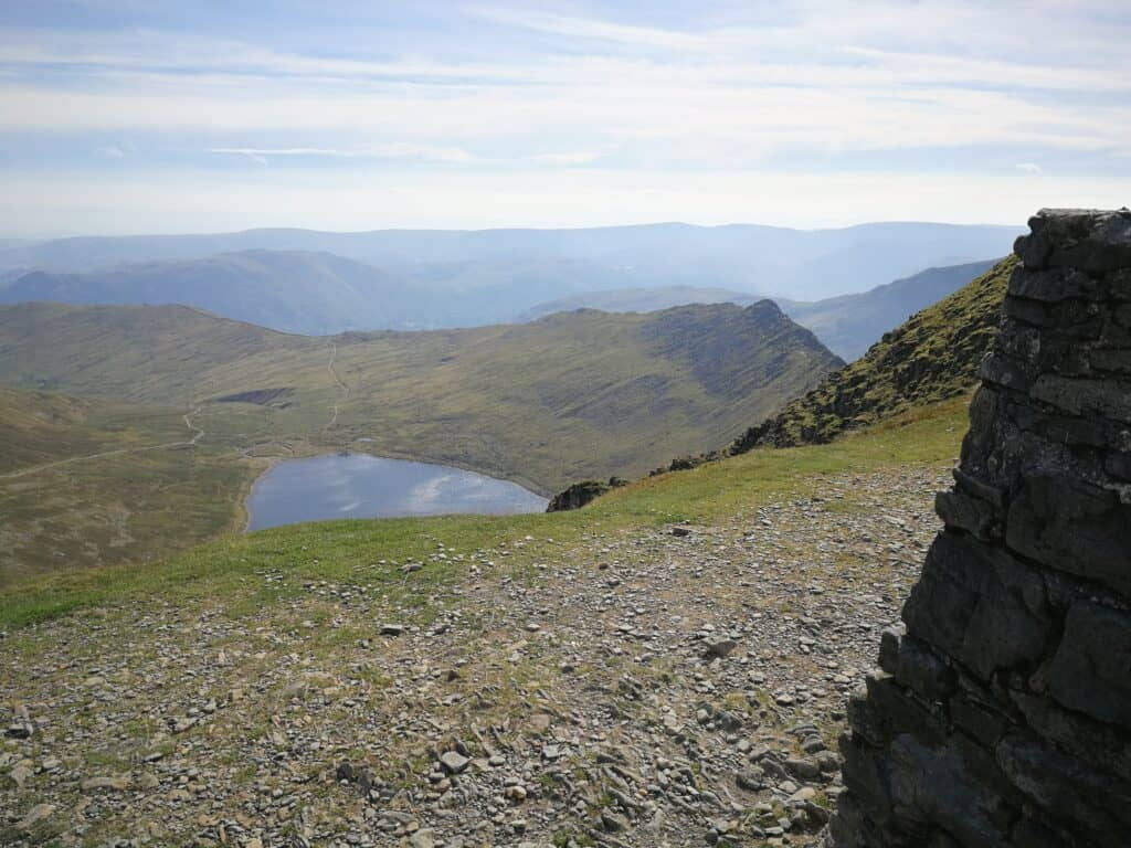 The summit trig of Helvellyn on our walk, with Red Tarn and Striding Edge on the right